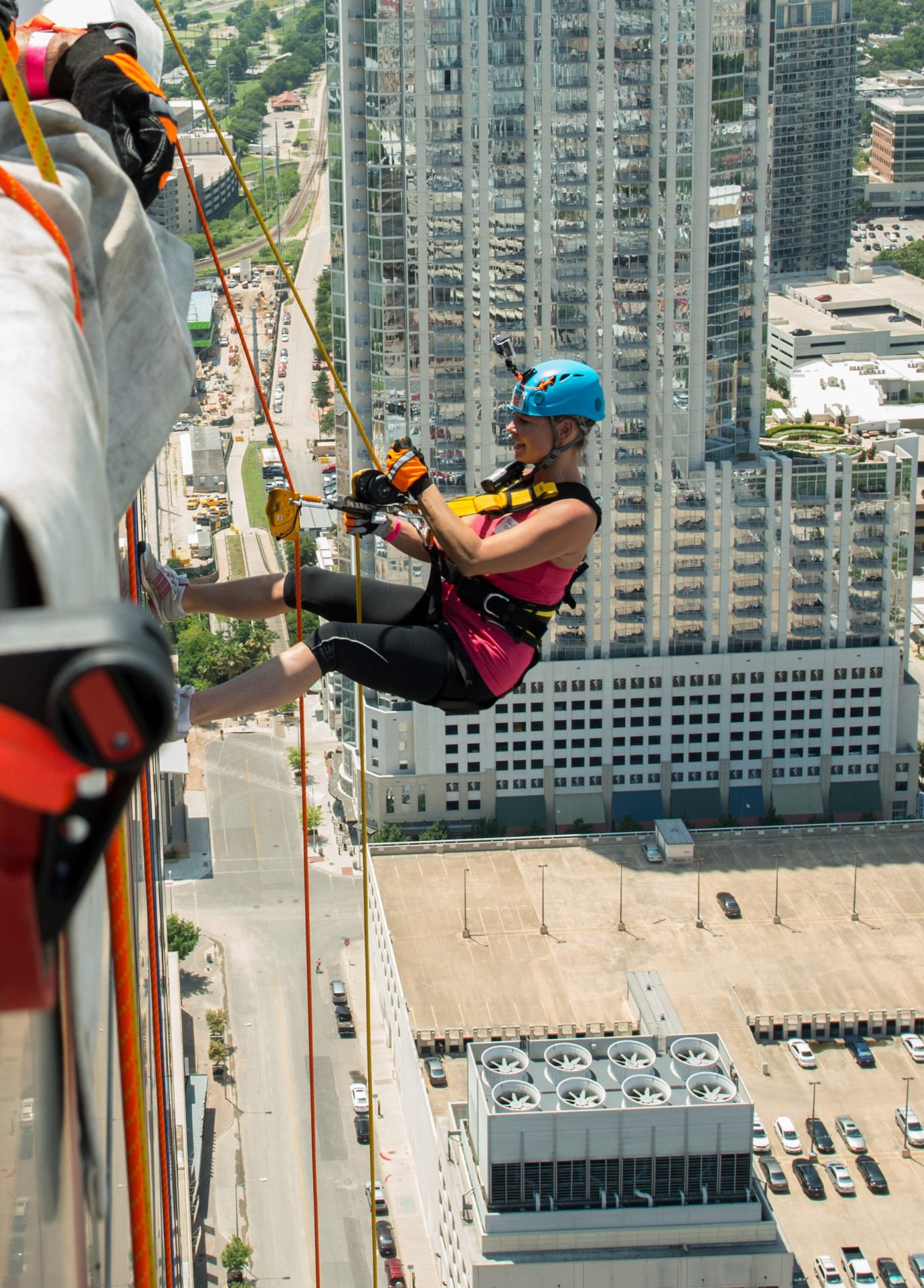 Image of woman rappelling over the edge of a building